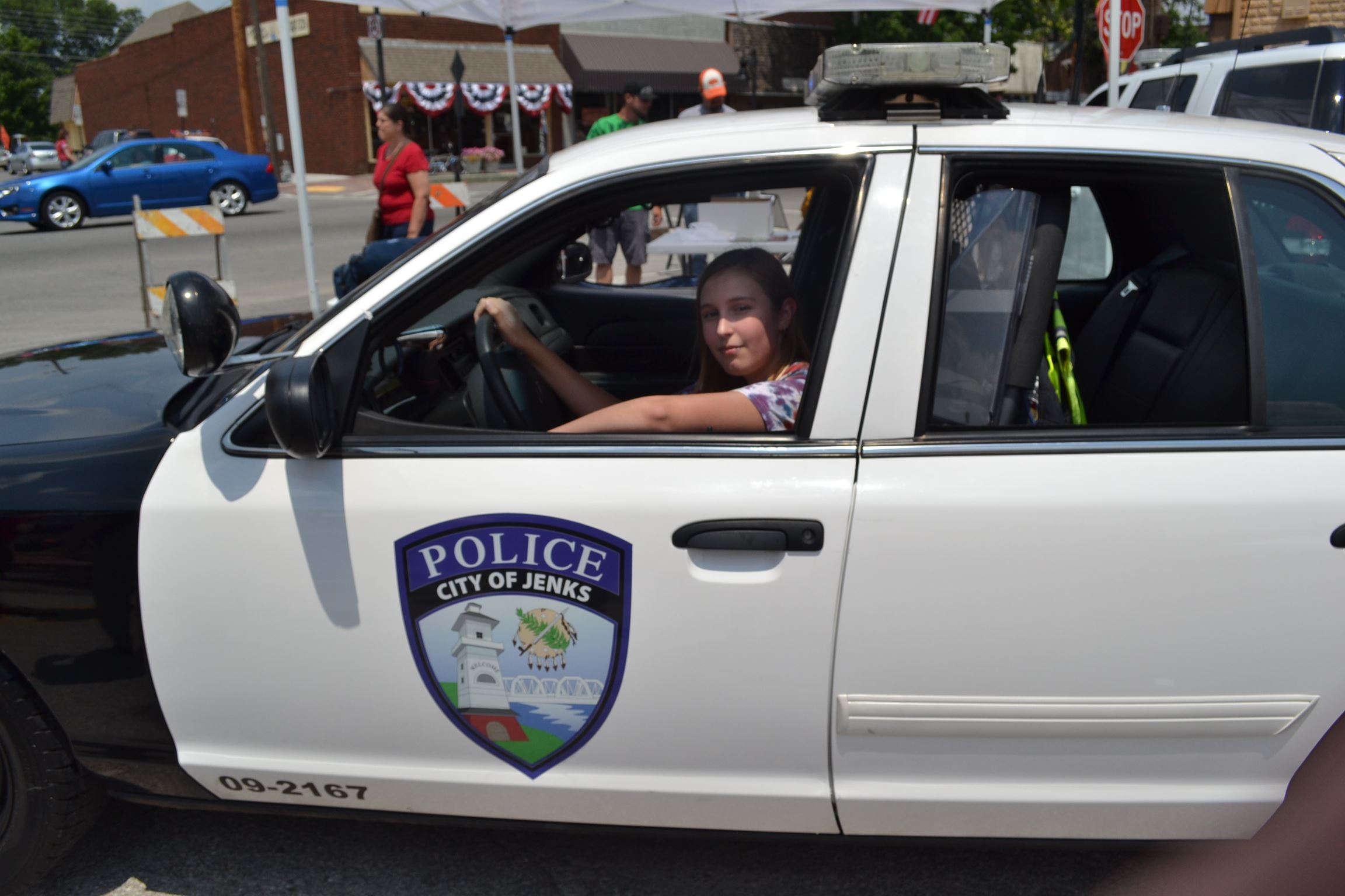 A Young Woman Behind the Wheel of a Police Cruiser