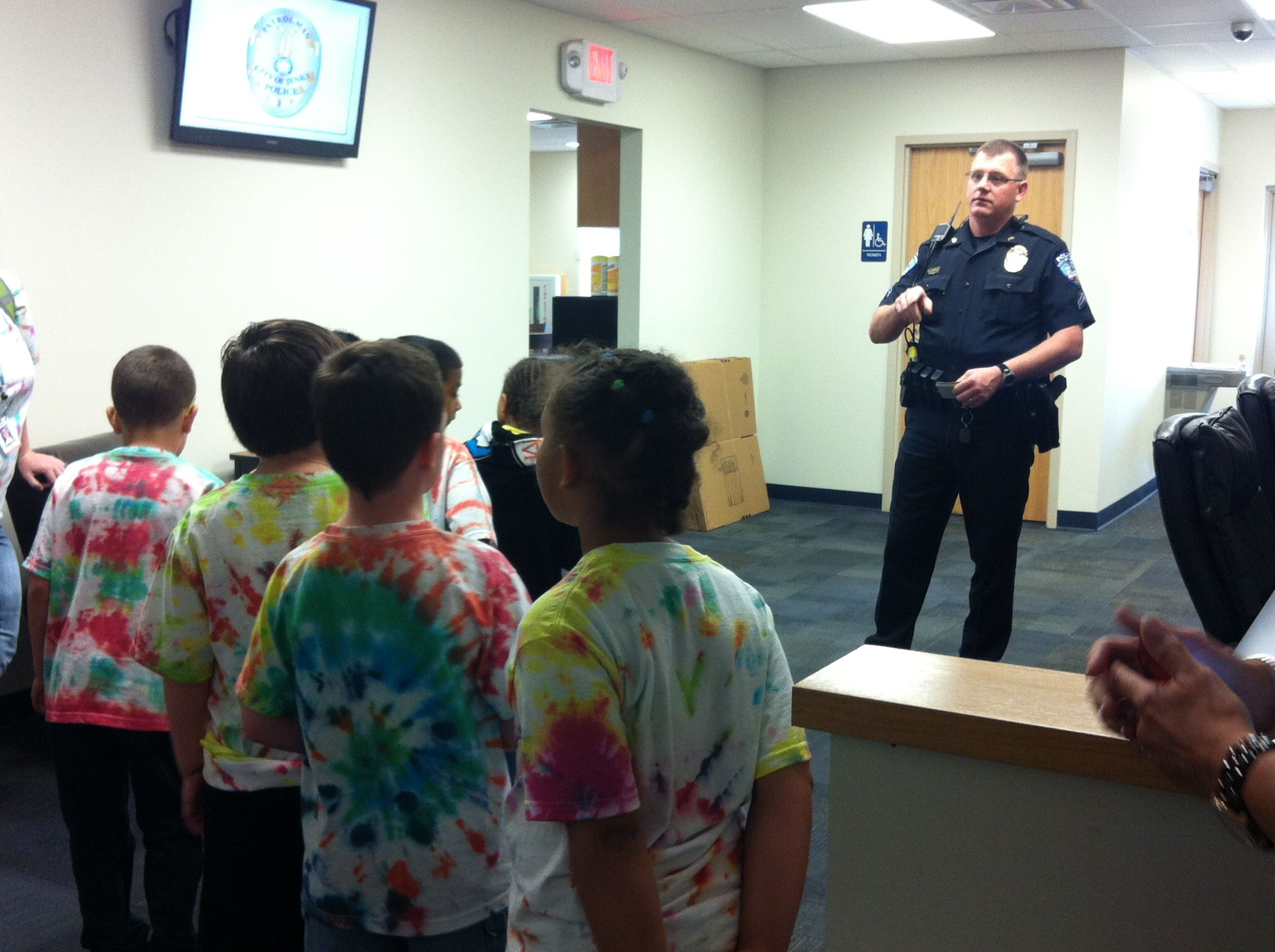 Officer Giving a Headquarters Tour to a Group of Kids in Tye Dye Shirts